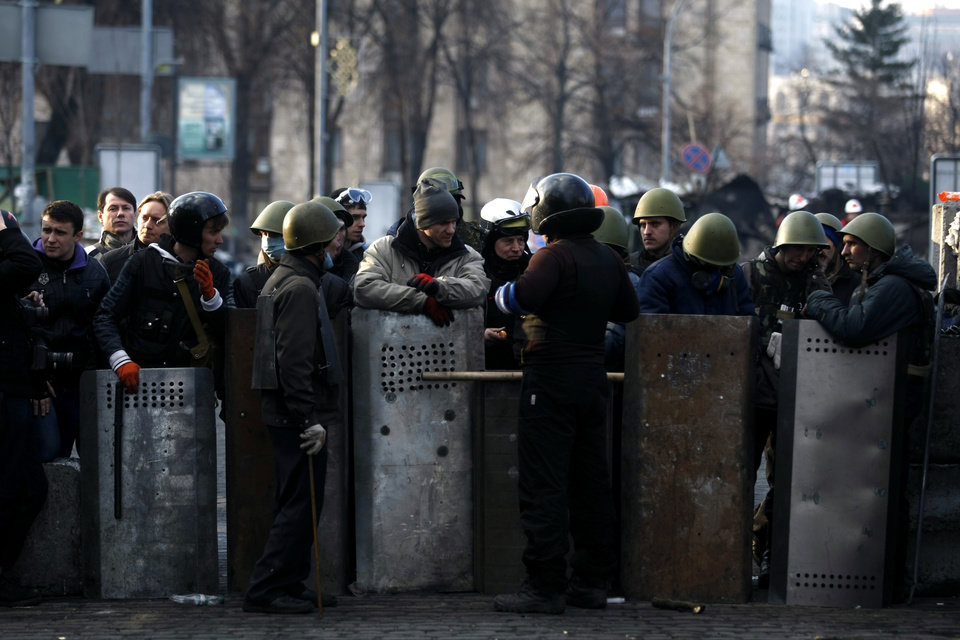 Photo - Anti-government protesters man a barricade on the outskirts of Independence Square in Kiev, Ukraine, Friday, Feb. 21, 2014. In a day that could significantly shift Ukraine's political destiny, opposition leaders signed a deal Friday with the country's beleaguered president that calls for early elections, a new constitution and a new unity government. (AP Photo/ Marko Drobnjakovic)