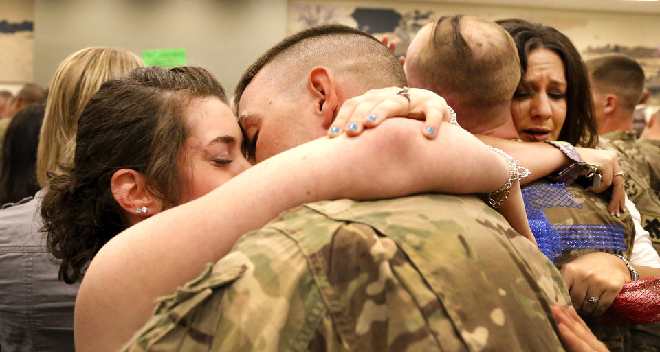 Photo - Kisses, hugs and tears are shared as troops are welcomed home. At least 1,000 people, mostly spouses, children, relatives and friends, crowded into a large room in the Armed Forces Reserve Center in Norman on Saturday, Sep. 28, 2013, to give a boisterous, and at times, tearful welcome  to members of the Oklahoma National Guard who returned to Norman after 10 months in Afghanistan. After a brief ceremony, which included a personal thank-you to his troops from Maj. Gen. Myles Deering, the soldiers were dismissed to an emotional reunion with their love ones. Deering serves as adjutant general of Oklahoma.  Photo  by Jim Beckel, The Oklahoman.