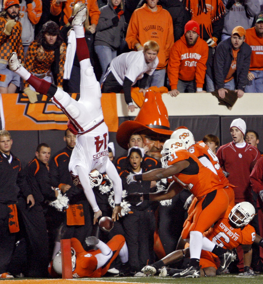 Oklahoma quarterback Sam Bradford (14) is flipped upside down as he leaps over Oklahoma State's Orie Lemon (41) during the second half of the college football game between the University of Oklahoma Sooners (OU) and Oklahoma State University Cowboys (OSU) at Boone Pickens Stadium on Saturday, Nov. 29, 2008, in Stillwater, Okla. STAFF PHOTO BY CHRIS  LANDSBERGER
