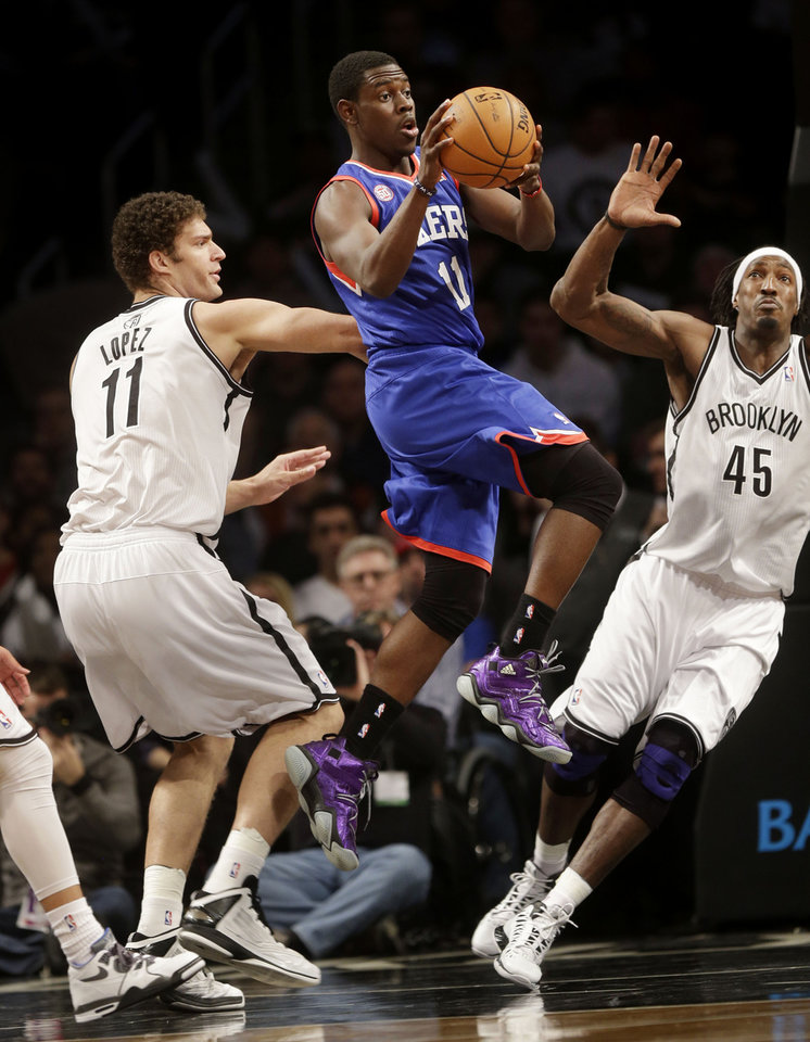 Philadelphia 76ers\' Jrue Holiday, center, looks to pass past Brooklyn Nets\' Brook Lopez, left, and Gerald Wallace during the first half of an NBA basketball game at the Barclays Center Sunday, Dec. 23, 2012 in New York. (AP Photo/Seth Wenig)