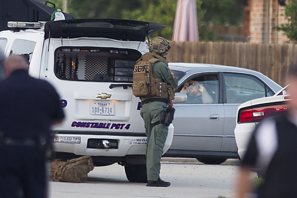 Photo - Law enforcement officers surround a shooting suspect in his car Wednesday, July 9, 2014, in Spring, Texas. Deputies cornered the suspect in a shooting at a suburban Houston home that resulted in multiple fatalities. (AP Photo/Houston Chronicle, Brett Coomer)