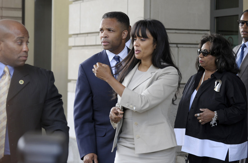 Photo - Former Illinois Rep. Jesse Jackson Jr., and his wife Sandra, leaves federal court in Washington, Wednesday, Aug. 14, 2013. Jackson was sentenced to two and a half years in prison Wednesday after pleading guilty to scheming to spend $750,000 in campaign funds on TV's, restaurant dinners, an expensive watch and other costly personal items. His wife received a sentence of one year.  (AP Photo/Susan Walsh)