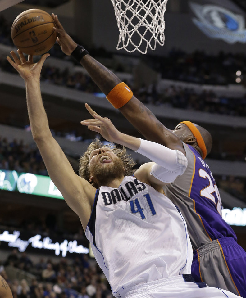 Photo - Dallas Mavericks forward Dirk Nowitzki (41), of Germany, has his shot blocked by Phoenix Suns center Jermaine O'Neal (20) during the second half of an NBA basketball game, Wednesday, April 10, 2013, in Dallas. The Suns won 102-91. (AP Photo/LM Otero)