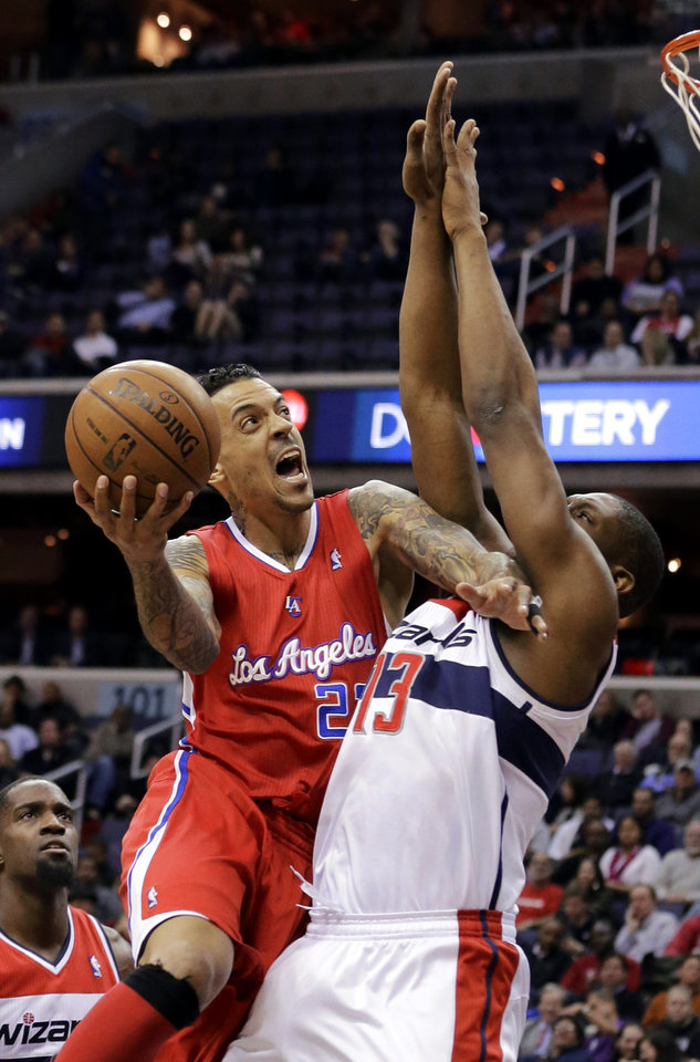 Photo - Los Angeles Clippers forward Matt Barnes (22) shoots in front of Washington Wizards forward Kevin Seraphin (13) from France, in the first half of an NBA basketball game Monday, Feb. 4, 2013 in Washington. (AP Photo/Alex Brandon)