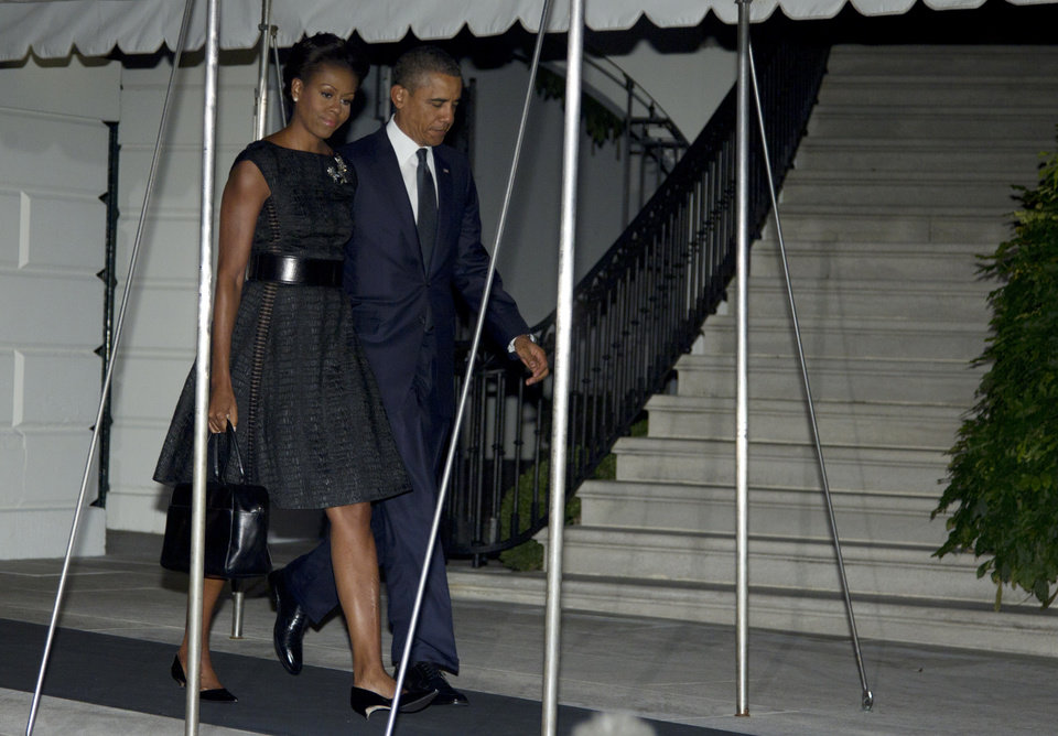 Photo -   President Barack Obama and first Lady Michelle Obama walk from residence across the South Lawn of the White House to board Marine One, Sunday, Sept. 11, 2011, in Washington, as they travel to New York to take part in the memorial service at ground zero. (AP Photo/Carolyn Kaster)