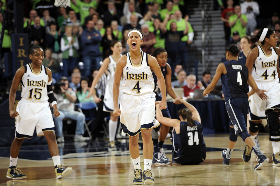 Photo - Notre Dame guard Skylar Diggins (4) celebrates a steal and the subsequent Connecticut foul during the third overtime of an NCAA college basketball game, Monday, March 4, 2013, in South Bend, Ind. Diggins scored 29 points as Notre Dame won 96-87 for the Big East regular-season title. Notre Dame guard Kaila Turner (15) also reacts to the play. (AP Photo/Joe Raymond)
