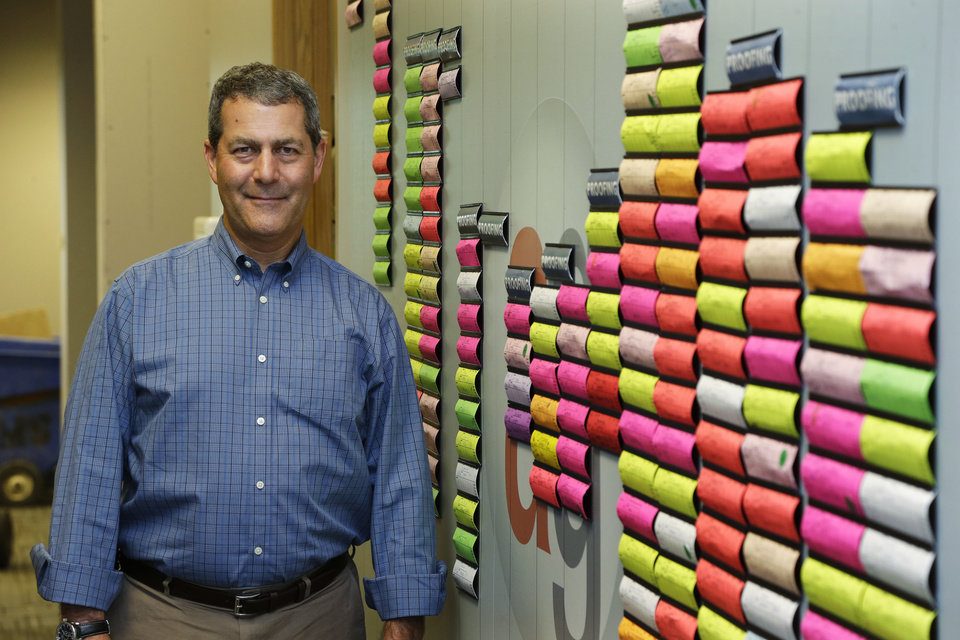 In this Monday, June 23, 2014 photo, Chuck Stempler, owner of an AlphaGraphics printing and marketing franchise, poses for a photo next to a wall that tracks current jobs for customers at his business, in Seattle. Stempler, who is a plaintiff in a federal lawsuit seeking to overturn a Seattle law that will raise the city's minimum wage to $15 from the current $9.32, says he will have to cut jobs to afford the higher wage. (AP Photo/Ted S. Warren)