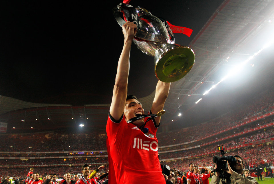 Photo - Benfica's Oscar Cardozo, from Paraguay, lifts the trophy celebrating at the end of their Portuguese league soccer match with Olhanense on Sunday April 20, 2014, at Benfica's Luz stadium in Lisbon. Benfica defeated Olhanense 2-0 to win the championship with two rounds left to play. (AP Photo/Francisco Seco)