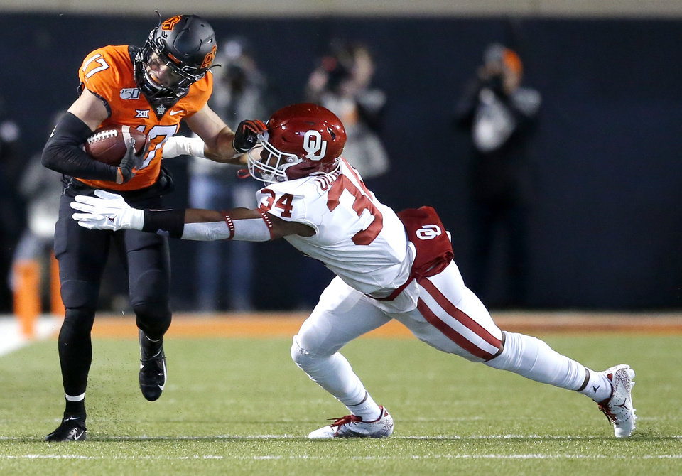 Photo - Oklahoma's David Ugwoegbu (34) tackles Oklahoma State's Dillon Stoner (17) in the first quarter during the Bedlam college football game between the Oklahoma State Cowboys (OSU) and Oklahoma Sooners (OU) at Boone Pickens Stadium in Stillwater, Okla., Saturday, Nov. 30, 2019. OU won  34-16. [Sarah Phipps/The Oklahoman]
