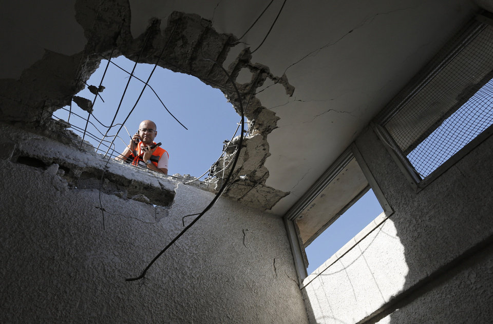 An Israeli police officer looks through a hole in the ceiling of a damaged house after a rocket fired by Palestinian militants from Gaza Strip landed in Ashkelon, southern Israel, Sunday, Nov. 18, 2012. Israel launched the operation last Wednesday by assassinating Hamas� military chief and carrying out dozens of airstrikes on rocket launchers and weapons storage sites. Over the weekend, the operation began to target Hamas government installations as well, including the offices of its prime minister. (AP Photo/Tsafrir Abayov)