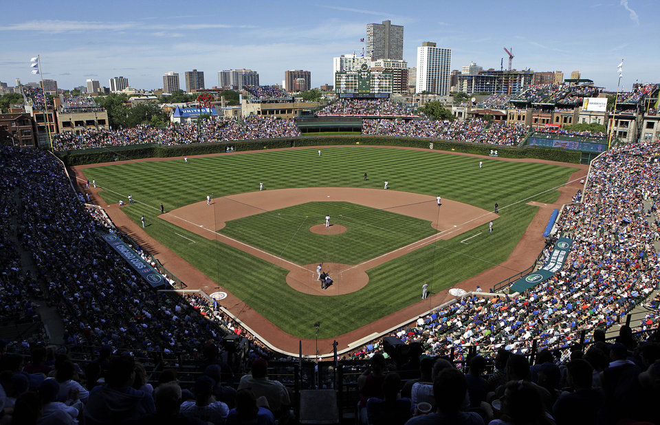 Photo - FILE - In this Aug. 4, 2013, file photo, the Los Angeles Dodgers play the Chicago Cubs at Wrigley Field in Chicago. Wrigley Field has been the site of so much heartbreak that some fans who spend their whole lives waiting for a winner ask their families, if they can pull it off, to sneak their ashes inside to be scattered in the friendly confines _ a final resting place to keep on waiting. But before years turned into decades and decades turned into a century without a World Series title, Wrigley Field was in first time and time again in changing the way we watch baseball and the experience for fans in ballparks around the country. The historic ballpark will celebrate it's 100th anniversary on April 23, 2014. (AP Photo/Kiichiro Sato, File)