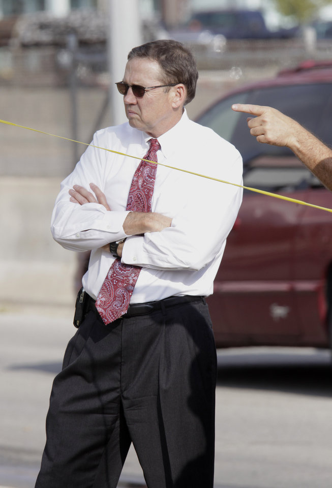 Photo - Oklahoma City police chief Bill Citty looking at a patrol car riddled with bullet holes sitting on Miller Avenue just south of NW 39 Street Monday, August 30, 2010. A female Oklahoma City police officer was shot in the car. Photo by Paul B. Southerland, The Oklahoman