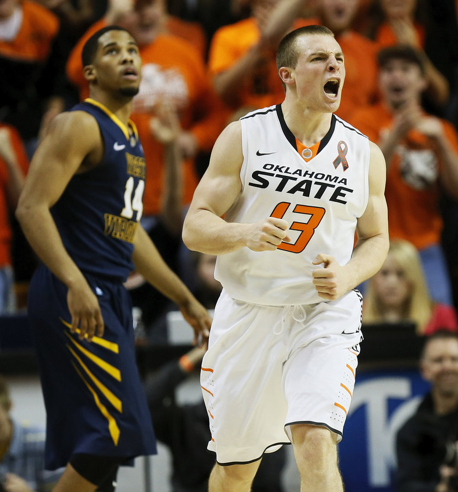 Oklahoma State\'s Phil Forte (13) reacts in front of West Virginia\'s Gary Browne (14) after hitting a 3-point shot during an NCAA men\'s basketball game between Oklahoma State University (OSU) and West Virginia at Gallagher-Iba Arena in Stillwater, Okla., Saturday, Jan. 26, 2013. Photo by Nate Billings, The Oklahoman
