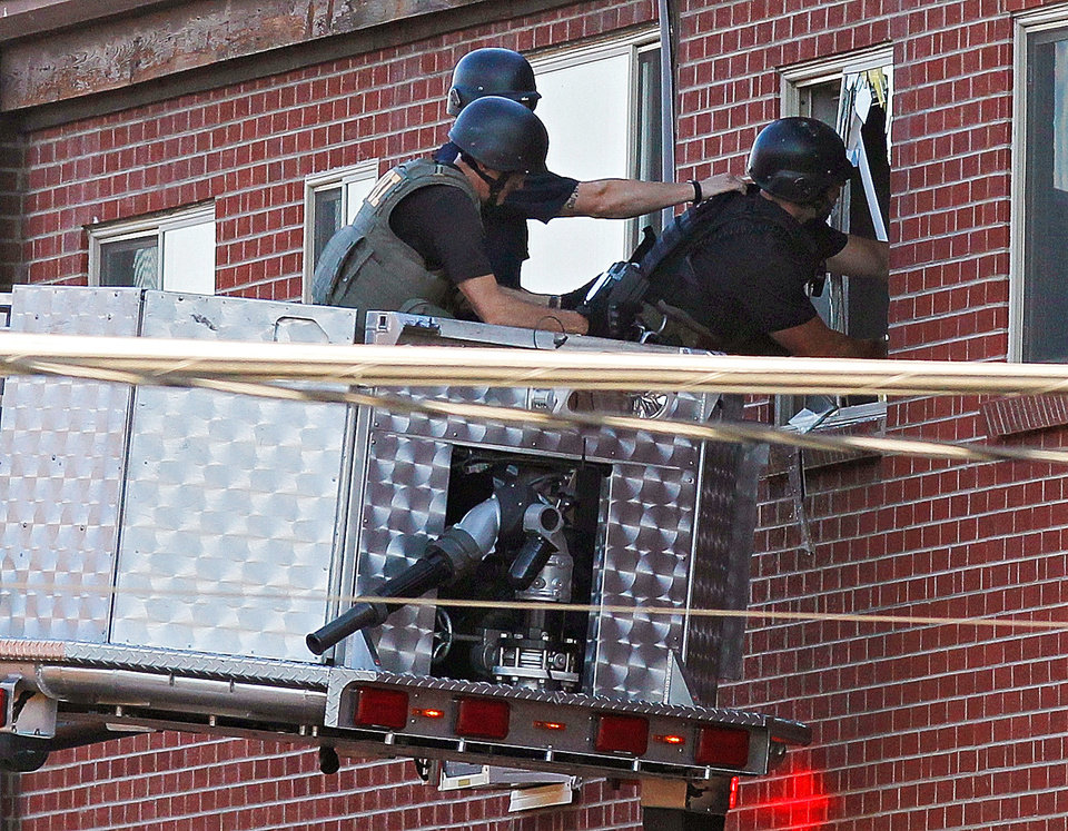 Photo - Police use a video camera to look inside an apartment  where the suspect in a shooting at a movie theatre lived in Aurora, Colo., Friday, July 20, 2012. As many as 12 people were killed and 50 injured at a shooting at the Century 16 movie theatre early Friday during the showing of the latest Batman movie. (AP Photo/Ed Andrieski) ORG XMIT: COEA110