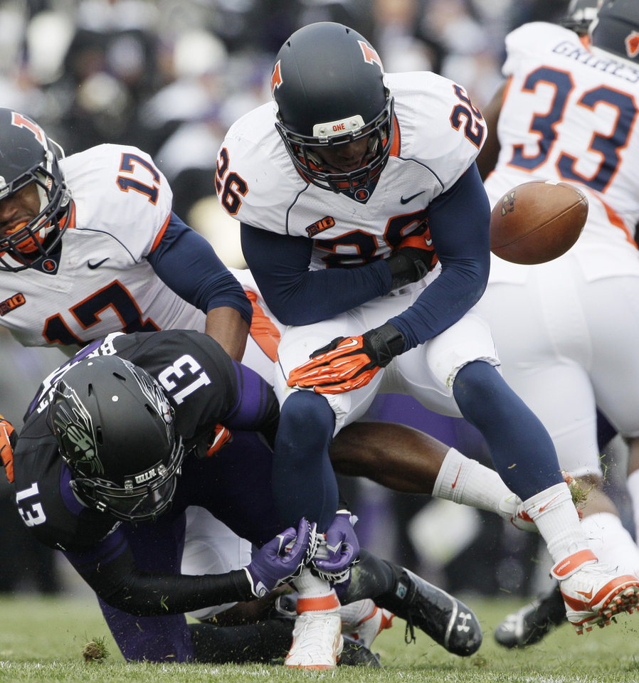 Photo -   Illinois kick returner Justin Green (26) fumbles the ball as he is hit by Northwestern cornerback C.J. Bryant (13)during the first half of an NCAA college football game in Evanston, Ill., Saturday, Nov. 24, 2012. Northwestern recovered the ball. (AP Photo/Nam Y. Huh)