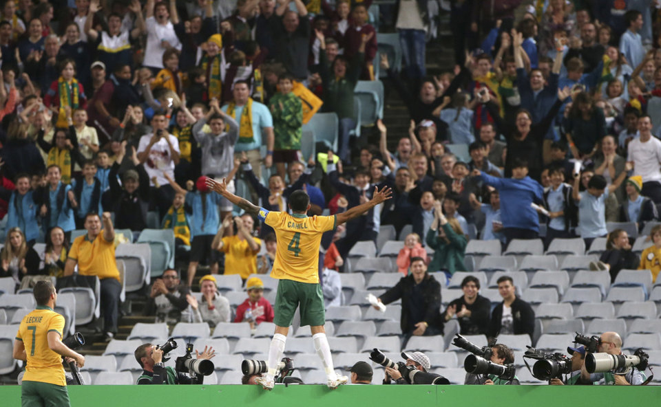 Photo - Australia's Tim Cahill stands on a fence and celebrates scoring a goal against South Africa during their friendly soccer match in Sydney, Monday, May 26, 2014. (AP Photo/Rick Rycroft)