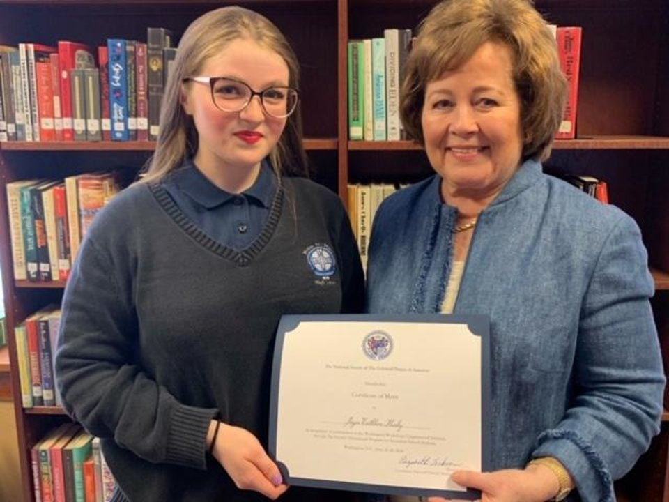 Photo -  Joyce Hanby, a junior at Mount St. Mary Catholic High School, left, receives a certificate from Marilyn Case, patriotic service chairman of the National Society of the Colonial Dames of America in the state of Oklahoma. [PHOTO PROVIDED]