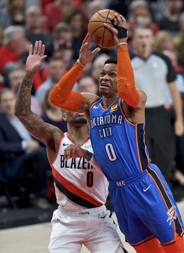 Photo - Oklahoma City Thunder guard Russell Westbrook, right, shoots next to Portland Trail Blazers guard Damian Lillard during the first half of Game 2 of an NBA basketball first-round playoff series Tuesday, April 16, 2019, in Portland, Ore. (AP Photo/Craig Mitchelldyer)
