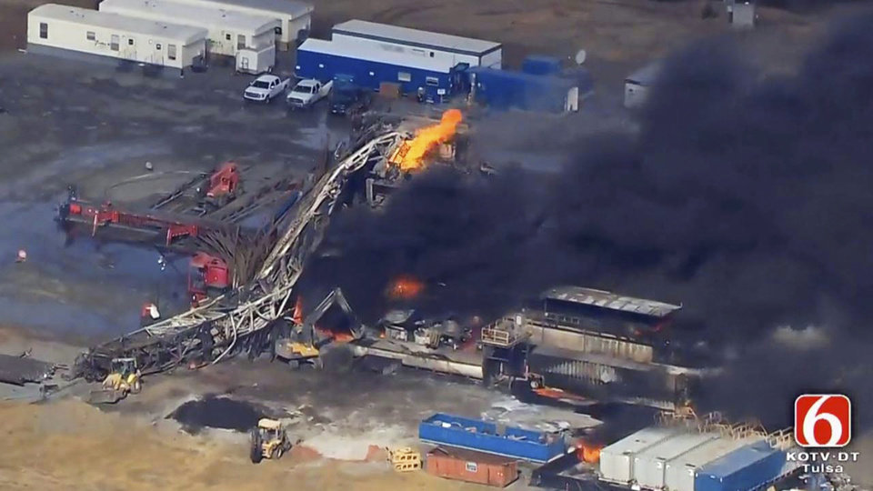 Photo -  In this Jan. 22, 2018, file photo from video by Tulsa's KOTV/NewsOn6.com, fires burn at an eastern Oklahoma drilling rig near Quinton, Okla. A Pittsburg County, Okla., jury has found National Oilwell Varco, a Houston-based company partially responsible for the 2018 explosion and fire that killed five men. The jury ordered the company to pay $1 million each to the estates of Josh Ray of Fort Worth, Texas, and Cody Risk of Wellington, Colorado. [Christina Goodvoice/KOTV/NewsOn6.com via AP, File]
