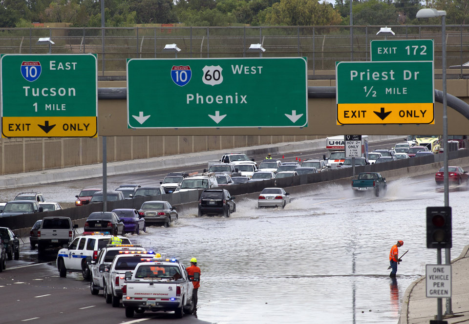 Crews work to drain the water after a storm caused flooding under the Kyrene overpass on the U.S. 60  in Tempe, Ariz., Sunday, July 21, 2013. (AP Photo/The Arizona Republic, Cheryl Evans)