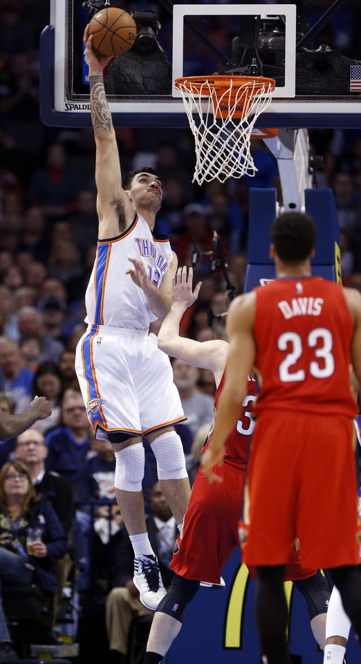 Photo - Thunder's Steven Adams (12) dunks int the first period during the NBA basketball game between the Oklahoma City Thunder and the New Orleans Pelicans at Chesapeake Energy Arena on Dec. 21, 2014 in Oklahoma City, Okla. Photo by Steve Sisney, The Oklahoman