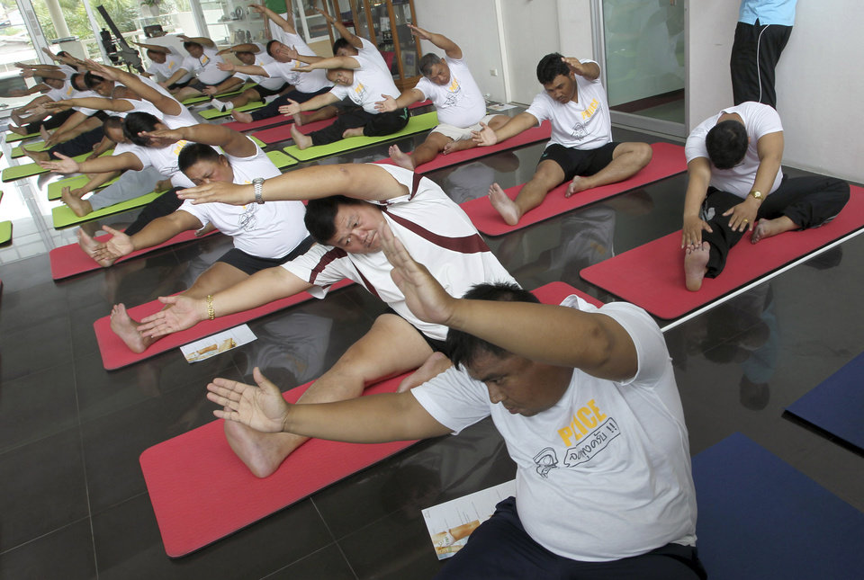 Photo - In this photo taken Thursday, July 4, 2013, Thai police officers take part in a yoga program at a police training center in Bangkok, Thailand. As part of a national effort to reduce the numbers of overweight officers, Thailand has opened a 12-day boot camp to get police into shape. This week, 60 overweight officers from around the country were sent to suburban Bangkok for dawn-to-dusk exercise and lecture programs on living more healthy. (AP Photo/Apichart Weerawong)