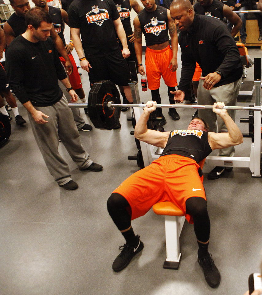 Photo - Safety Zack Craig lifts weights during a workout at Oklahoma State's pro day held at Boone Pickens Stadium in Stillwater on Thursday, March 13, 2014. Photo by KT King, The Oklahoman