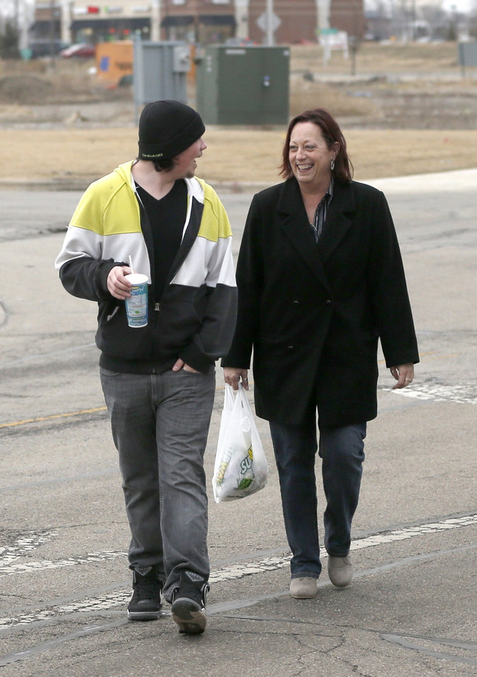 Photo - In this Friday, March 21, 2014 photo, Cody Lewis, left, a recovering heroin addict, laughs with his mother, Karen, as they walk back to their suburban Chicago home from a Wal-Mart store in Aurora, Ill.