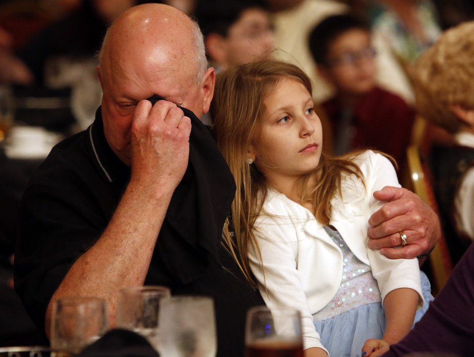 Photo -  Bruce Dees and his granddaughter, Claire, 8, listen as his son and her father, trooper Nicholas Dees, is honored during the Trooper of the Year Awards on Wednesday in Norman. Photo by Steve Sisney, The Oklahoman   STEVE SISNEY -  THE OKLAHOMAN