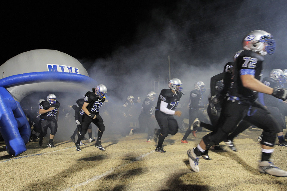 Photo - The Guthrie Bluejays take the field during a high school football game between Guthrie and East Central at The Rock in Guthrie, Friday, Nov. 18, 2011.  Photo by Garett Fisbeck, The Oklahoman