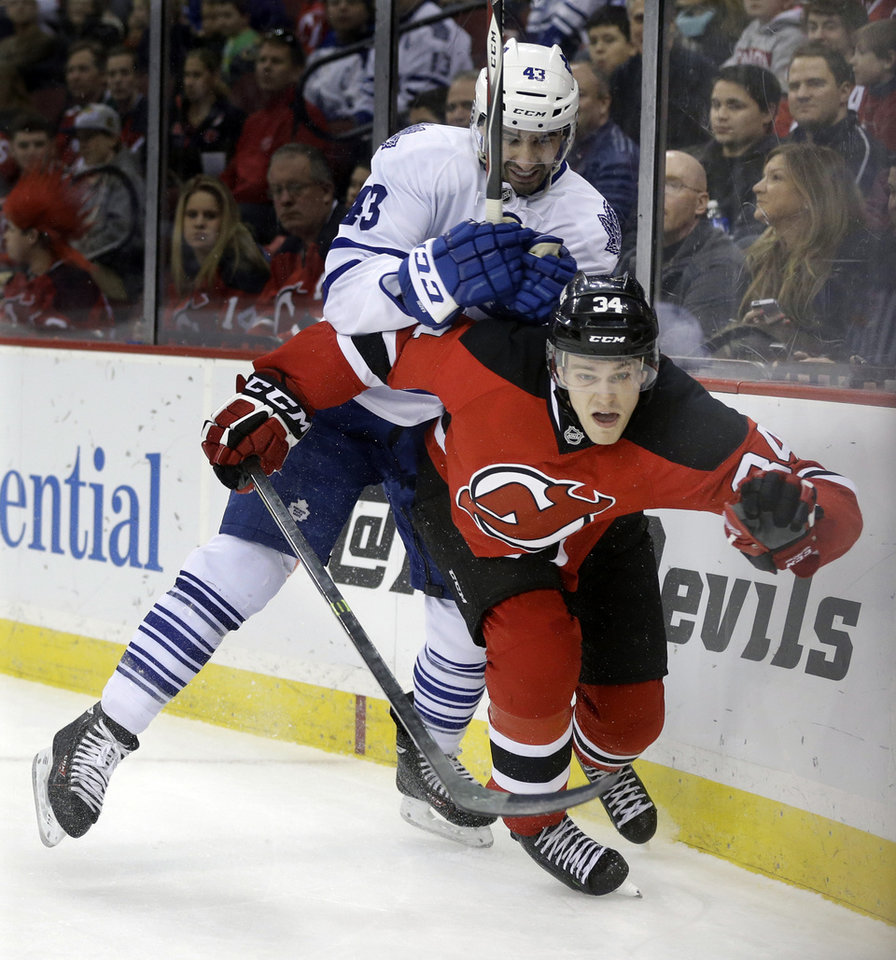 Photo - New Jersey Devils' Jon Merrill (34) is hit by Toronto Maple Leafs' Nazem Kadri (43) during the first period of an NHL hockey game, Sunday, March 23, 2014, in Newark, N.J. (AP Photo/Mel Evans)
