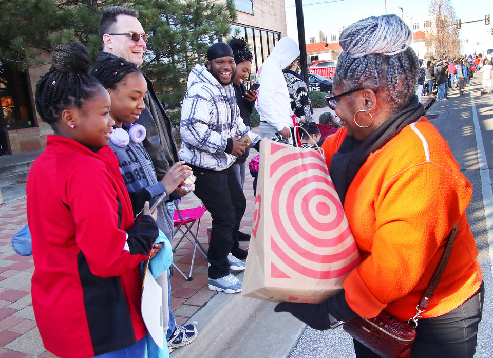 Photo - A woman with the Douglass High School Alumni Association passes out candy at the MLK Day Parade along Walker Ave. during celebrations of Dr. Martin Luther King, Jr. holiday, Monday, January 20, 2019. [Photo by Doug Hoke/The Oklahoman]