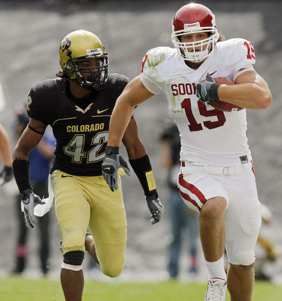 Photo - Oklahoma's Joe Jon Finley (19) races past Colorado's Benjamin Burney (42) as Finley  takes the ball up field during the first half of the college football game between the University of Oklahoma Sooners (OU) and the University of Colorado Buffaloes (CU) at Folsom Field in Boulder, Co., on Saturday, Sept. 28, 2007. 
