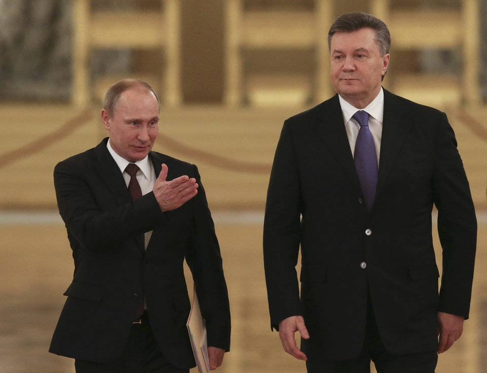 Photo - FILE - In this Tuesday, Dec. 17, 2013 file photo Russian President Vladimir Putin, left, shows the way to his Ukrainian counterpart Viktor Yanukovych during a meeting in the Kremlin in Moscow, Russia. Moscow on Wednesday granted Ukrainian President Viktor Yanukovych protection
