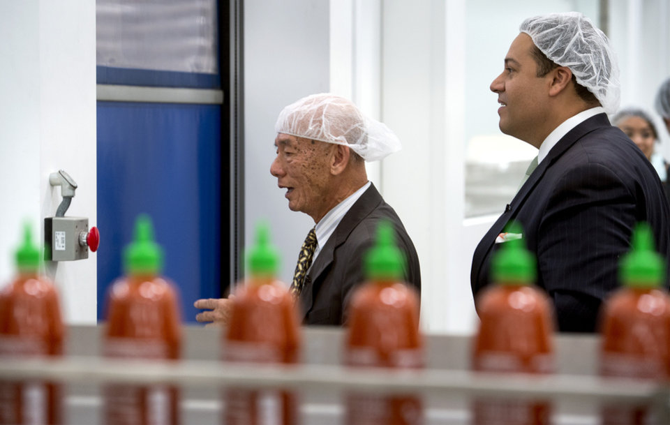Photo - Texas State Representative Jason Villalba, right, of Dallas, Texas, tours the Huy Fong Foods, Inc. manufacturing plant, maker of Sriracha hot sauce, with founder and CEO David Tran, in Irwindale, Calif. May 12, 2014.  Texas officials are trying to convince the Sriracha maker to move to their state after the city of Irwindale declared them a public nuisance. (AP Photo/San Gabriel Valley Tribune,  Leo Jarzomb)