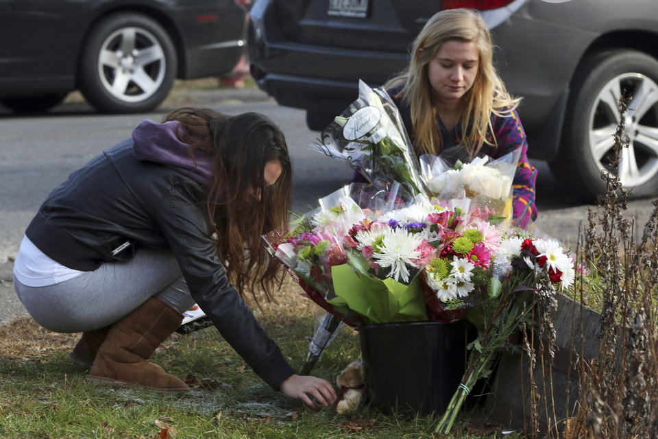 Photo - Mourners places flowers and a teddy bear at a makeshift memorial at a sign for the Sandy Hook school,  Saturday, Dec. 15, 2012 in Sandy Hook village of Newtown, Conn.  The massacre of 26 children and adults at Sandy Hook Elementary school elicited horror and soul-searching around the world even as it raised more basic questions about why the gunman, 20-year-old Adam Lanza, would have been driven to such a crime and how he chose his victims.  (AP Photo/Mary Altaffer) ORG XMIT: CTMA112