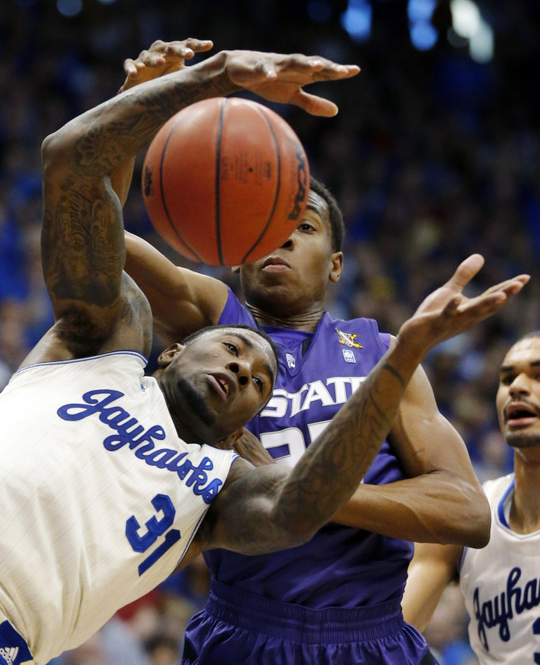 Photo - Kansas forward Jamari Traylor (31) rebounds against Kansas State guard Wesley Iwundu during the first half of an NCAA college basketball game in Lawrence, Kan., Saturday, Jan. 11, 2014. (AP Photo/Orlin Wagner)