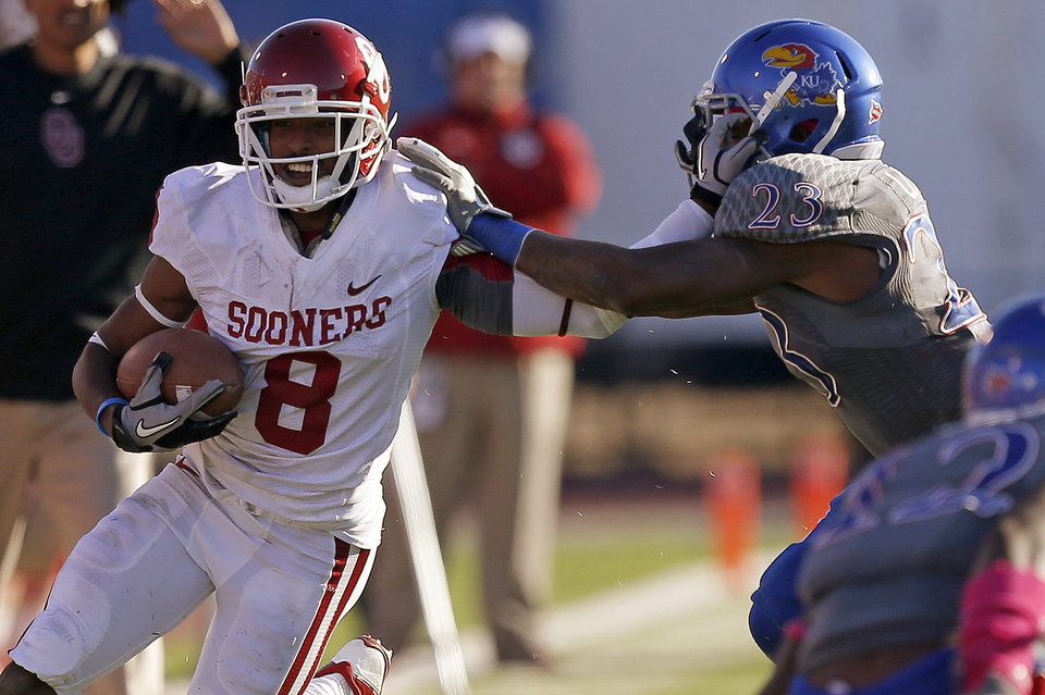 Photo - OU's Jalen Saunders (8) fights off KU's Dexter Linton (23) during the college football game between the University of Oklahoma Sooners (OU) and the University of Kansas Jayhawks (KU) at Memorial Stadium in Lawrence, Kan., Saturday, Oct. 19, 2013. Oklahoma won 34-19. Photo by Bryan Terry, The Oklahoman