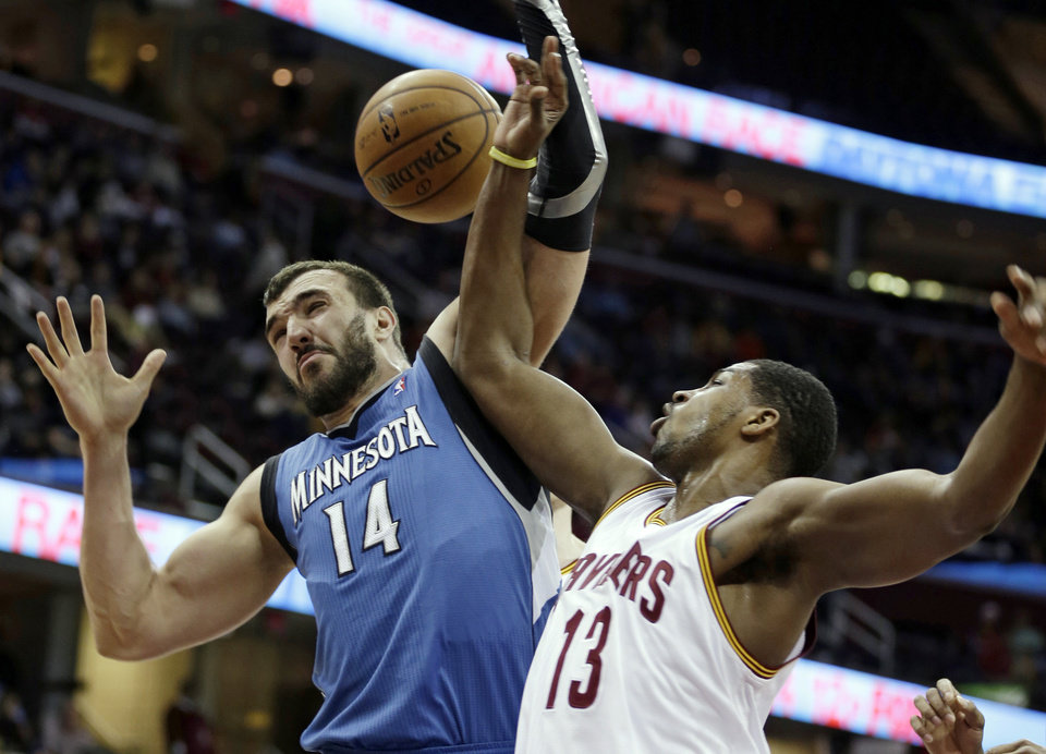 Minnesota Timberwolves' Nikola Pekovic (14), from Montenegro,  and Cleveland Cavaliers' Tristan Thompson (13) battle for a rebound during the first quarter of an NBA basketball game Monday, Feb. 11, 2013, in Cleveland. (AP Photo/Tony Dejak)