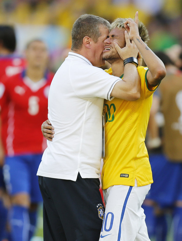 Photo - Brazil's Neymar embraces a member of his team after the penalty shootout at the World Cup round of 16 soccer match between Brazil and Chile at Mineirao Stadium in Belo Horizonte, Brazil, Saturday, June 28, 2014. Brazil won 3-2 on penalties after Neymar scored the winner in the shootout. (AP Photo/Frank Augstein)