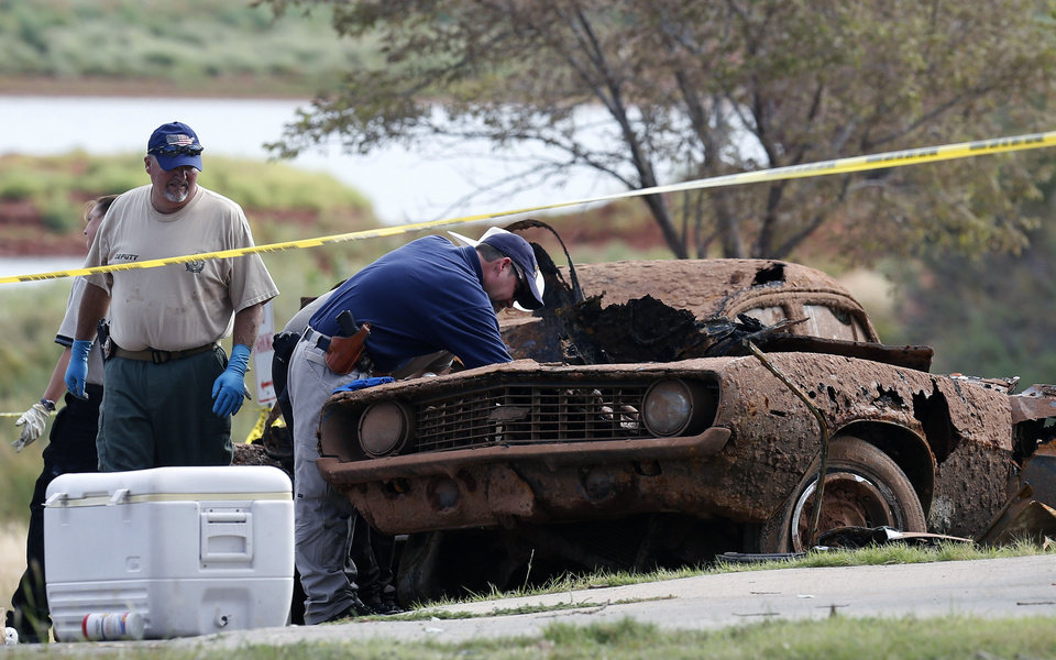 Photo - Law enforcement officials from multiple agencies examine the two cars pulled from Foss Lake, in Foss, Okla., Wednesday, Sept. 18, 2013. The Oklahoma State Medical ExaminerÂ's Office says authorities have recovered skeletal remains of multiple bodies in the Oklahoma lake where the cars were recovered. (AP Photo/Sue Ogrocki) ORG XMIT: OKSO105
