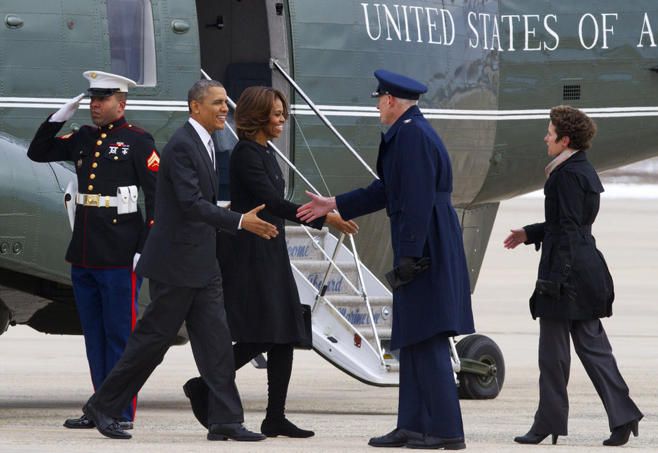 Photo - A Marine salutes as President Barack Obama and first lady Michelle Obama are greeted by 89th Airlift Wing Commander Col. David Almand and his wife Cathy Almand at Andrews Air Force Base, Md., Friday, March 7, 2014, before boarding Air Force One for a trip to Florida. (AP Photo/Jacquelyn Martin)