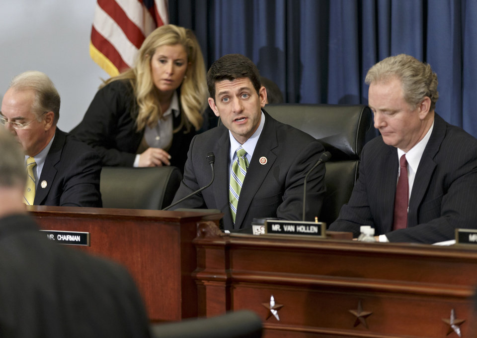 Photo - House Budget Committee Chairman Rep. Paul Ryan, R-Wis., center, presides over a markup session where House Republicans are crafting a budget-balancing plan that sharply cuts spending on transportation, health care programs for the middle class and the poor, food stamps and other domestic initiatives, Wednesday, April 2, 2014, on Capitol Hill in Washington. Ryan is flanked by Rep. Chris Van Hollen, D-Md., right, the committee's ranking member, and Rep. Tom Price, R-Ga., left.  (AP Photo/J. Scott Applewhite)
