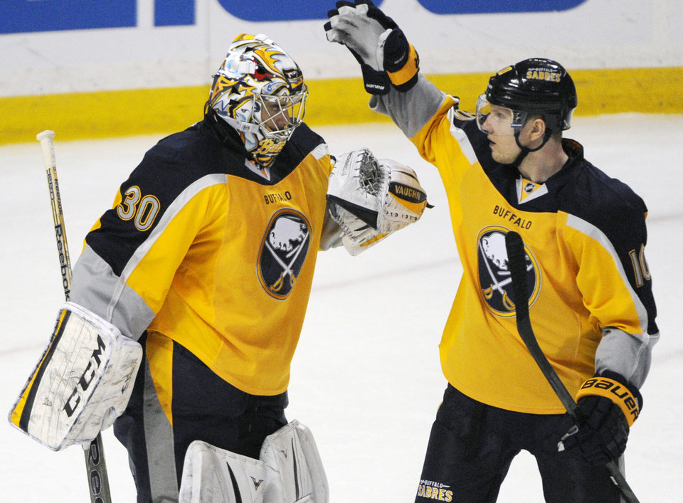 Photo - Buffalo Sabres' Ryan Miller (30) celebrates with Christian Ehrhoff (10) after defeating the New Jersey Devils during an NHL hockey game in Buffalo, N.Y., Saturday, Jan. 4, 2014. Buffalo won 2-1. (AP Photo/Gary Wiepert)