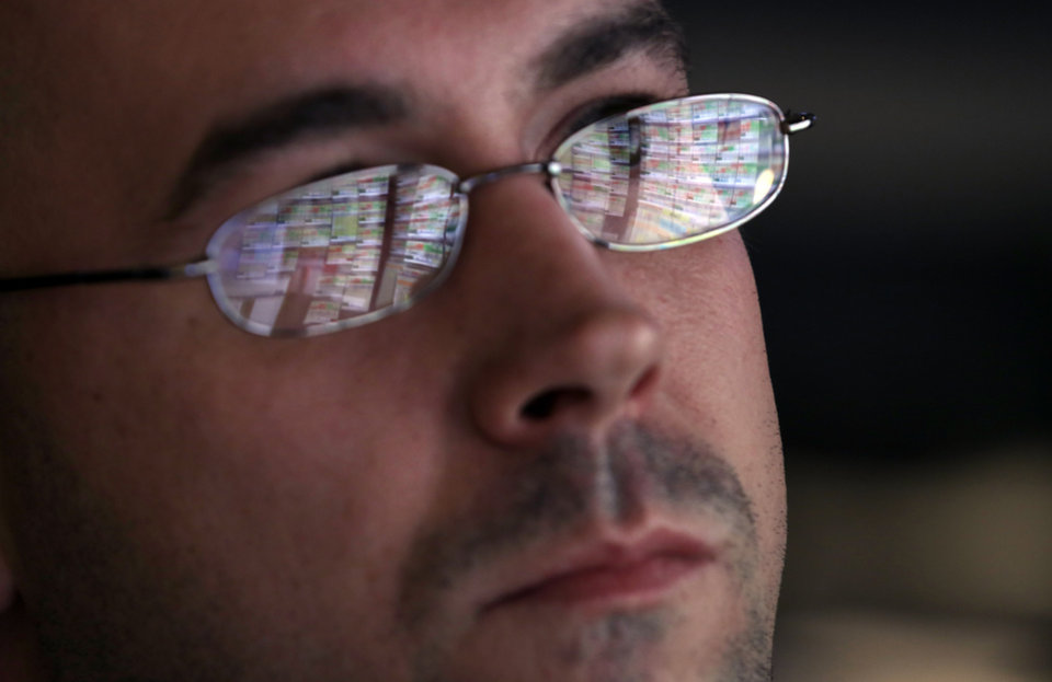 Photo - The screens of specialist Jarret Johnson are reflected in his glasses as he works at his post on the floor of the New York Stock Exchange Thursday, Oct. 10, 2013. Wall Street roared in approval Thursday after Washington appeared to break an impasse that threatened to push the country into default.  (AP Photo/Richard Drew)