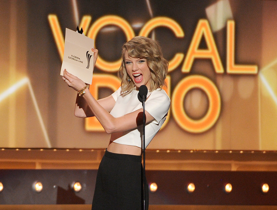 Photo - Taylor Swift presents the vocal duo of the year award to Florida Georgia Line at the 49th annual Academy of Country Music Awards at the MGM Grand Garden Arena on Sunday, April 6, 2014, in Las Vegas. (Photo by Chris Pizzello/Invision/AP)