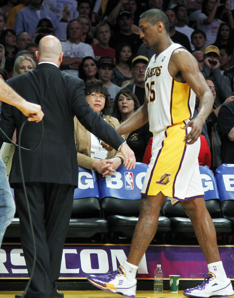 Photo -   Los Angeles Lakers trainer Gary Vitti, left, escorts Metta World Peace from the court after he was ejected for double flagrant fouls against the Oklahoma City Thunder in the first half of an NBA basketball game in Los Angeles, Sunday, April 22, 2012. The Lakers won in double overtime, 114-106. (AP Photo/Reed Saxon)