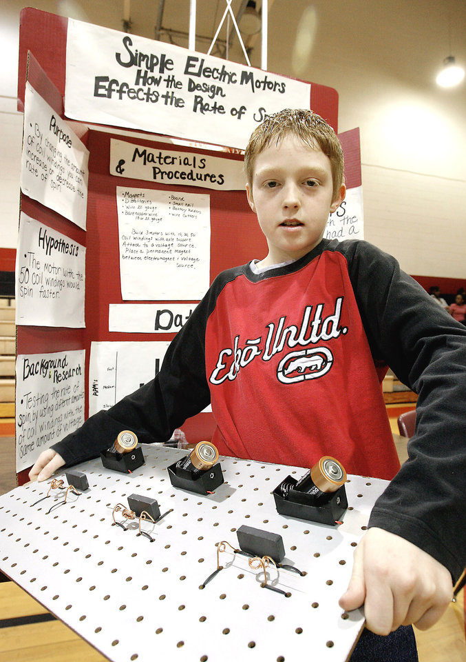 "Photo - Sixth-grader Casey Jones, 11, shows his project, ""Simple Electric Motors, How the Design Effects the Rate of Spin."""