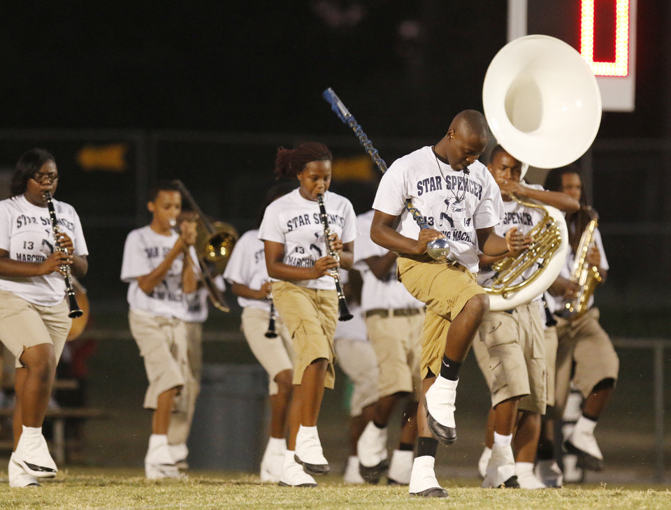 Photo - Drum Major Deron Gabriel leads the band onto the field at the half. The Star Spencer band performs during halftime of the high school football game between Millwood and Star Spencer in Spencer, Thursday, September 5, 2013. Photo by Doug Hoke, The Oklahoman