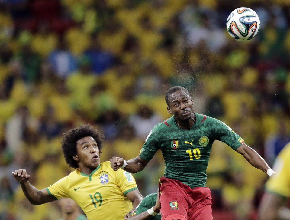 Photo - Brazil's Willian watches as Cameroon's Vincent Aboubakar heads the ball during the group A World Cup soccer match between Cameroon and Brazil at the Estadio Nacional in Brasilia, Brazil, Monday, June 23, 2014. (AP Photo/Bernat Armangue)